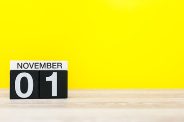 November 1st. Day 1 of month, wooden color calendar on yellow background. Autumn time. Empty space for text