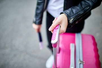 Pink suitcase close-up with hand girl on handle