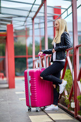 A girl is standing by the railing with a pink suitcase