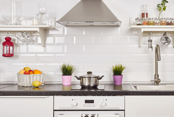 Interior of a light kitchen in the apartment. Bright home interior decoration items, fruit, flowers in a pot, steel hood. Bright ready-made picture for your individual design