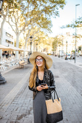 Young woman tourist in hat walking on the famous pedestrian boulevard in Barcelona city
