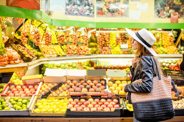 Woman standing in front of the food store showcase with fruits and vegetables
