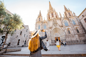 Autocollant pour porte Barcelona Young woman tourist photographing with phone famous saint Eulalia church during the morning light in Barcelona city