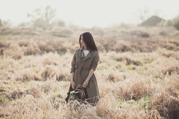 Asian girl with a backpack in the wilted fields