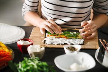 Woman Making Veggie Maki Sushi Rolls