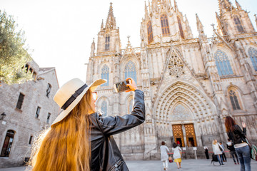 Foto auf Acrylglas Barcelona Young woman tourist photographing with phone famous saint Eulalia church during the morning light in Barcelona city