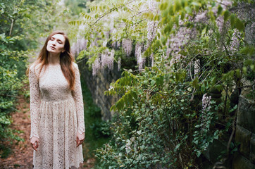Beautiful young woman standing among wisteria
