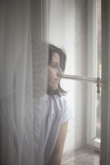 Young beautiful woman looking through the window