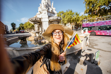 Young woman tourist making selfie photo with catalan flag near the fountain in Barcelona city