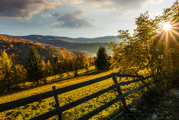 wooden fence in rural area at autumn sunrise. beautiful scenery in mountains