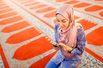 Young muslim woman with smartphone in mosque