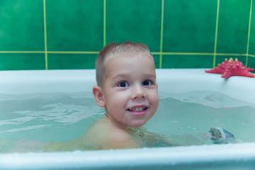 Boy in white bath tub on white background