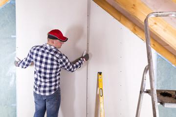 Construction worker holding gypsum board. Attic renovation. Installation of drywall