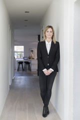 Portrait of businesswoman in black suit jacket in her stylish home