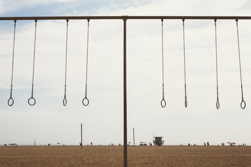Exercise equipment along beach in Santa Monica, Pacific Ocean in distance, Los Angeles, CA, USA