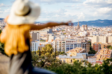 Young woman tourist in hat enjoying great cityscape view on Barcelona. Woman is out of focus