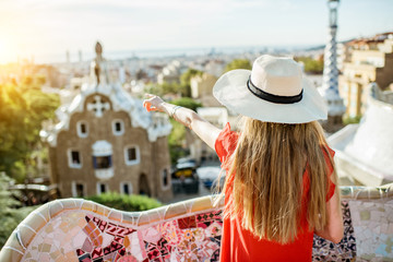 Young woman tourist in red dress enjoying great view on Barcelona city in famous Guell park