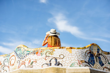 View on the beautiful terrace decorated with mosaic with happy woman tourist in Guell park in Barcelona