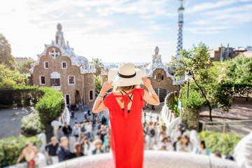 Woman tourist in red dress enjoying great view standing on the terrace in famous Guell park in Barcelona