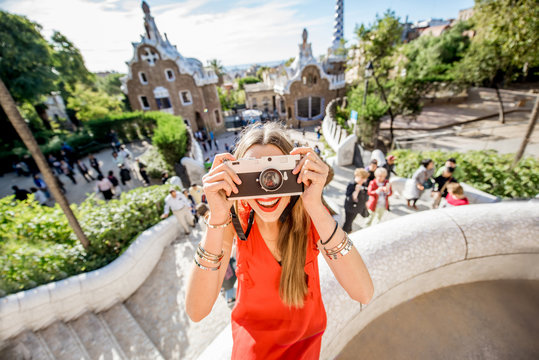 Woman tourist in red dress having fun visiting famous Guell park in Barcelona