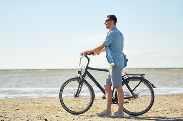 happy young man with bicycle on beach