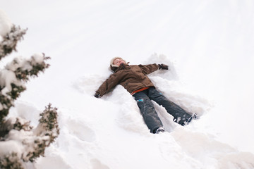 Young boy making a snow angel.