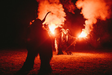 two krampus making fire show with bengal light
