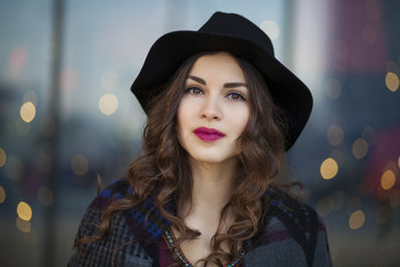 Young beautiful woman with black curly hair and red lipstick walking in the city
