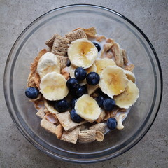 A healthy bowl of cereal with bananas and blueberries