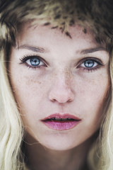 Portrait of a beautiful young woman with freckles and blue eyes