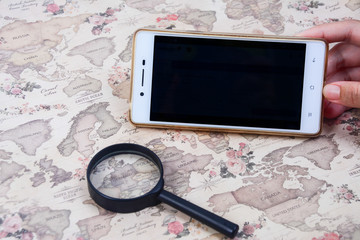 A hand holding a mobile phone with blank screen, with a magnifying glass on a world map background.