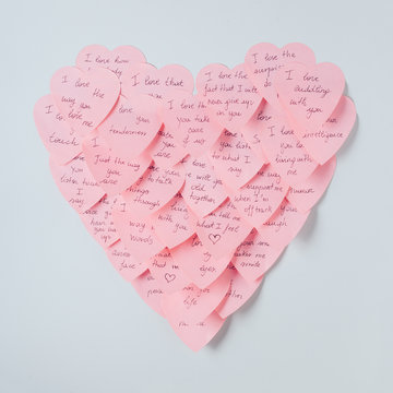 Pink heart made with adhesive notes against a white background