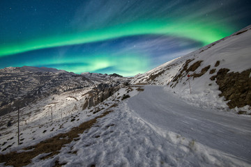 northern Lights above the snowy mountains