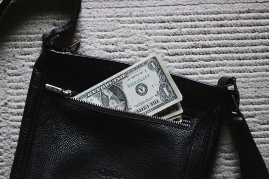 Dollar sticking out of a black bag