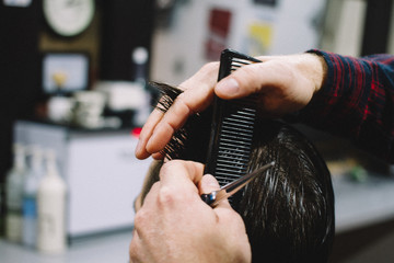 Barber cuts young male hair