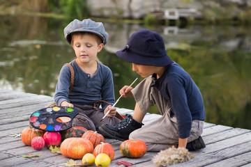 Friendly kids paint small Halloween pumpkins