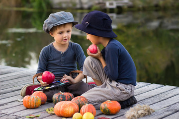 Two cheerful boys paint small apples