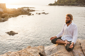 Young man meditating on the rock above the ocean