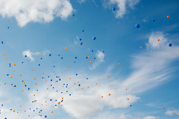 Blue and orange balloons in the sky