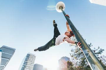 Man holding on to lamp post in mid air during a parkour training