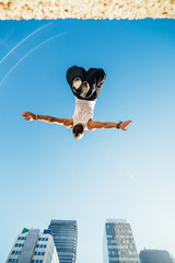 Nadir photography of a man doing a backflip in the air during a parkour training in a city