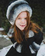 Little girl smiles for the camera in winter