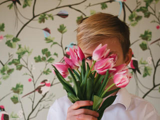 A pre-teenage boy with a bunch of pink tulips partially obscuring his face.