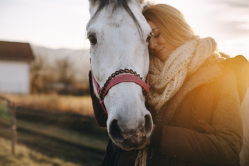 Woman and a horse holding their heads together