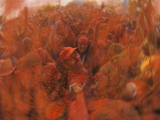 A couple taking a selfie in the crowd at a crazy festival all in orange colour made of holi powder