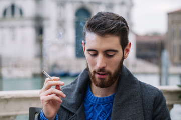 Portrait of a stylish man outdoors with cigarette