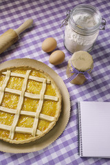 Apricot pie with ingredients and notepad