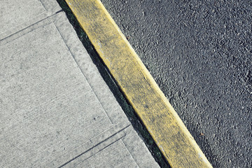 Painted curb along sidewalk and urban street