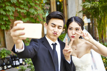 young asian bride and groom taking a selfie