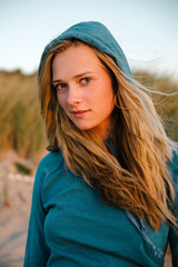 Beautiful young blonde woman in blue hoodie at the beach